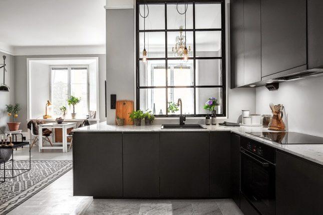 Het marmeren keukenblad steelt de show in deze stoere keuken met zwarte kasten. Klik hier voor meer foto's.