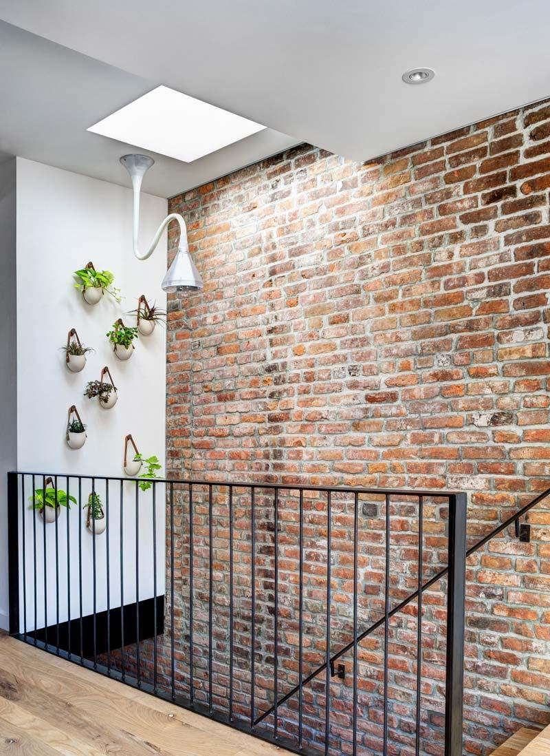 zwarte stalen trapleuning bakstenen muur