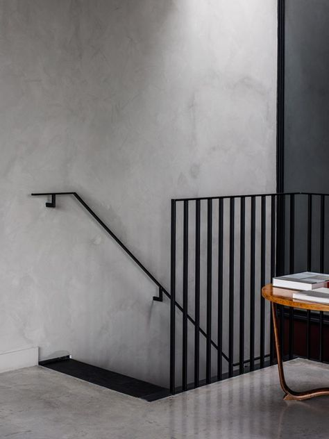 zwarte stalen trapleuning betonstuc muur