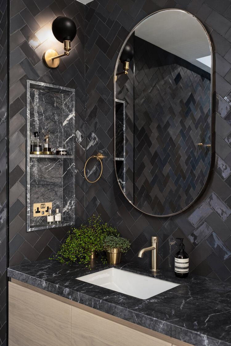 zwarte visgraat wandtegels badkamer ovalen spiegel